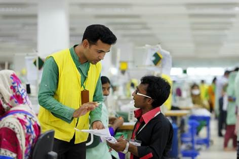 A worker with a disability and his colleague are discussing, Bangladesh